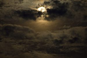 A full moon covered by dark clouds